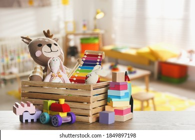 Set of different cute toys on wooden table in children's room