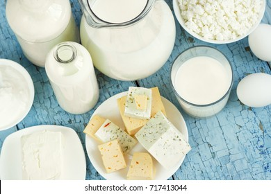 Set of different dairy products on the blue wooden background, top view