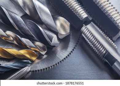 set of different drill bits,thread tap and mill cutters on steel plate background. Locksmithing deal.