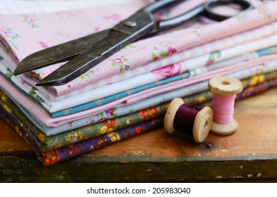 Set of different fabrics, wooden thread spools and tailor scissors on wooden background with selective focus on scissors
