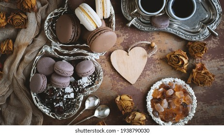 a set of different French macaroons for tea and coffee. Chocolate and vanilla macaroons with coffee and caramel sugar on a wooden table. top view. the heart for the text.