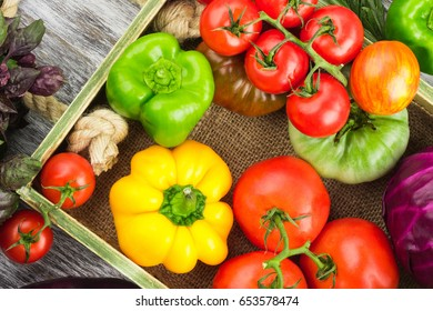 Set of different fresh raw colored vegetables and fruits in the wooden tray, light background