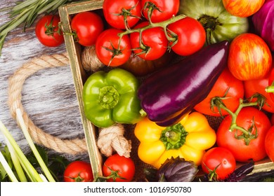 Set of different fresh raw vegetables in the wooden tray, light background, top view