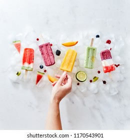 A set of different frozen berry smoothies lolly on a stick with years and fruits. The girl's hand takes a smoothie on a stick from ice cubes. Flat lay