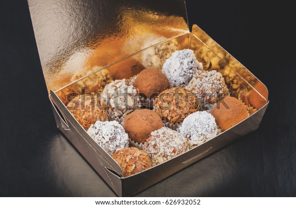 Set of different kinds of homemade chocolate truffles in a golden box. Toned.