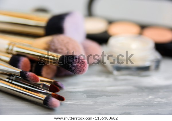 Set of different makeup brushes on gray background. Copy space, soft focus