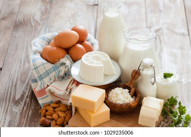 Set of different milk products on ristic wooden table. Milk, cottage cheese, cheese, cream, kefir