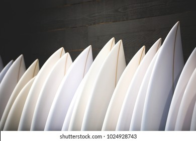 Set of different new white surf boards in a stack.