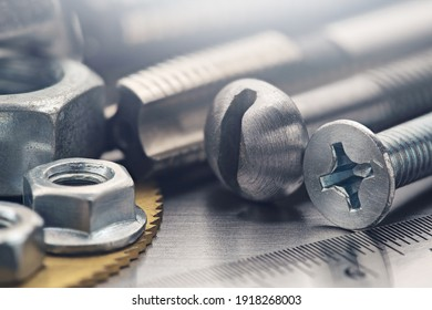 set of different nuts, bolts, screws, washers and drill bits,thread tap and mill cutters on steel plate background. Locksmithing deal.