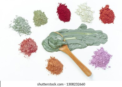 Set of different pile of cosmetic clay mud powders and wet clay in wooden spoon in the middle, on white