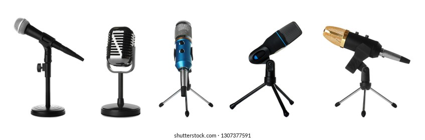 Set of different professional microphones in holders on white background