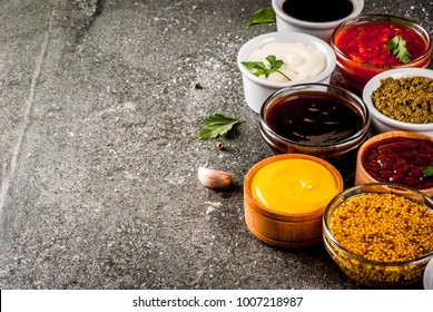 Set of different sauces - ketchup, mayonnaise, barbecue, soy, teriyaki, mustard, grain hills, pesto, adzhika, chutney, tkemali, pomegranate sauce on black stone background. Copy space