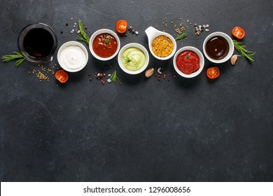 Set of different sauces - ketchup, mayonnaise, barbecue, soy, teriyaki, mustard, pesto, adzhika, oil on dark background. Top view. Flat lay. Copy space