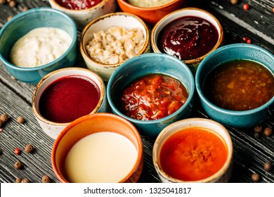 Set of different sauces on black wooden background. Top view