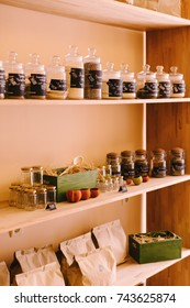 Set of different spices and herbs in glass jars on wooden shelves, racks. Healthy food ingredients - choice of herbs, seeds. Curry, saffron, turmeric, pepper, salt and rosemary.