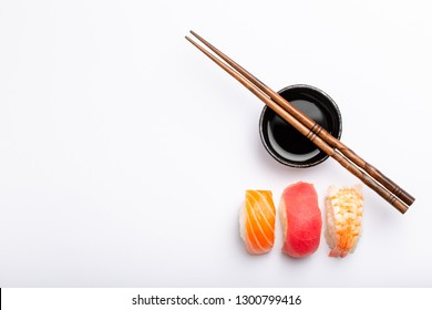 Set of different sushi nigiri, soy sauce and chopsticks over white background with copy space, top view. Traditional Japanese sushi concept, close-up