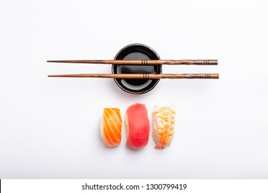 Set of different sushi with salmon, tuna and shrimp, soy sauce and chopsticks over white background, top view. Traditional Japanese sushi concept, close-up, flat lay