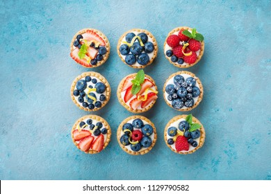 Set of different tartlets or cake with cream cheese and summer berry. Pastry dessert top view.