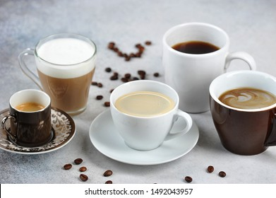 Set of different types of coffee in different cups. Espresso, cappuccino, Americano, latte are presented. Coffee beans on the surface of a light table.