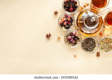 A set of different types of green, black and herbal tea next to the kettle filled with hot brewed tea on a beige background. Delicious organic drinks. View from above. A place for text.