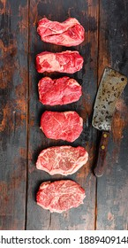 A set of different types of raw beef steaks:top blade, rump, chuck eye roll over old wooden background top view with butcher cleaver