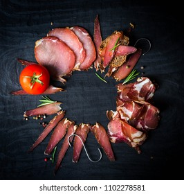 A set of different types of raw smoked meat. Jamon Lomo, ?oppa and fillet on a black background.