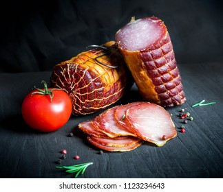 A set of different types of raw smoked meat. Jamon Lomo, сoppa and fillet on a black background.