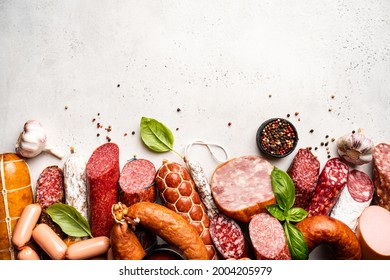 Set of different types of sausages, salami and smoked meat with basil and spices on white background. Top view.