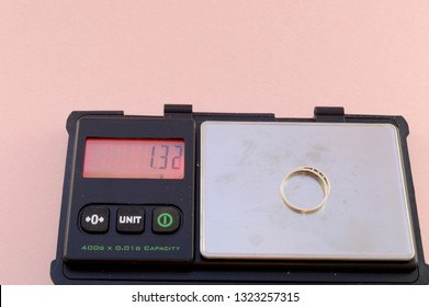 A set of digital scales weighs a gold ring that is going to be sold for scrap.