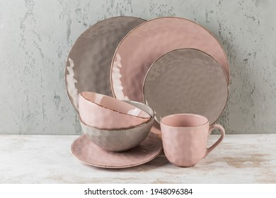 A set of dishes made of plates, bowls and mugs in pink and brown on a gray background side view with a copy space for text. The concept of dishes for food. Horizontal orientation.
