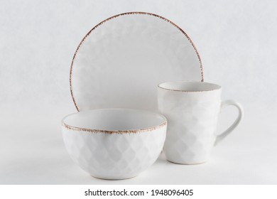 A set of dishes made of plates, bowls and mugs of white color on a light background close-up, isolated. The concept of dishes for food. Horizontal orientation.
