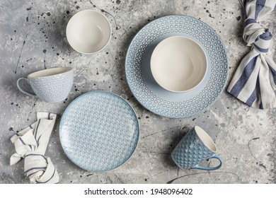 A set of dishes from plates, bowls and mugs of gray color in a serving with napkins on a gray background top view. The concept of dishes for food. Horizontal orientation