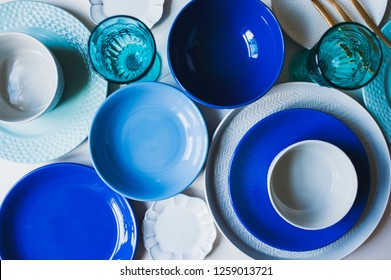 set of dishware in blue tones. Ceramic plates and wine glasses top view