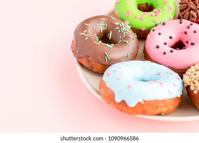 Set of donuts covered with a variety of glaze and sprinkled with sweets on a plate on a pink background