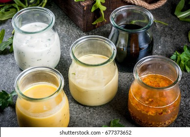 Set of dressings for salad: sauce vinaigrette, mustard, mayonnaise or ranch, balsamic or soy, basil with yogurt. Dark stone table. On background of greenery, vegetables for salad. Copy space