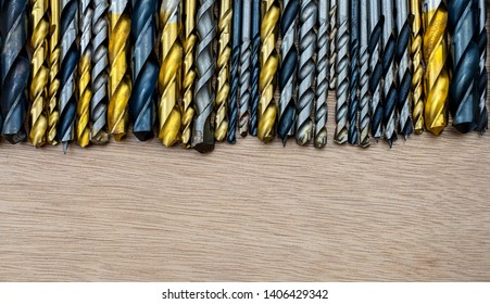 Set of drill bits different sizes for wood and concrete on wooden background