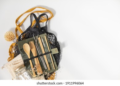 Set of Eco friendly bamboo cutlery and mesh bags on white background