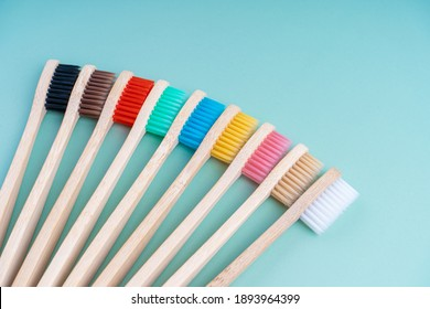 A set of Eco-friendly antibacterial toothbrushes made of bamboo wood on a light green background. Environmental care trends.