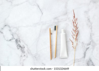 Set of eco-friendly toothbrushes and toothpaste on marble background. Dental and healthcare concept. Top view, flat lay. Free copy space.