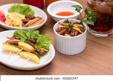 Set of Edible insect food with woodworm, french fries and vegetable in the white plate on table background. Close up, Selective focus