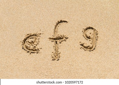 Set of efg letters of alphabet written on sand with lower case.