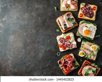 Set of eight different sandwiches with meat, copy space for design or text. Top view or flat lay. Assortment meat toasts on black background. Idea, creative concept for sausage maker