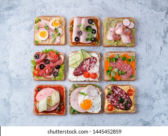 Set of eight different sandwiches with meat in square shape. Top view or flat lay. Assortment meat toasts on gray cement background. Idea, creative concept for sausage maker