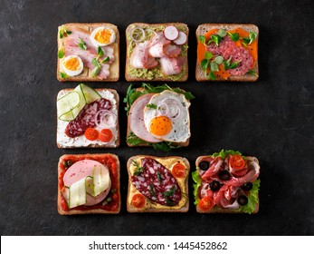 Set of eight different sandwiches with meat in square shape, copy space for text. Top view or flat lay. Assortment meat toasts on black background. Idea, creative concept for sausage maker