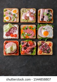 Set of eight different sandwiches with meat in square shape, copy space for text. Top view or flat lay. Assortment meat toasts on black background. Idea, creative concept for sausage maker. Vertical