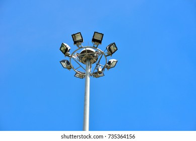 Set of eight floodlights mounted on metal post with blue sky background, Lighting pole tower at the sports stadium, car park and ground