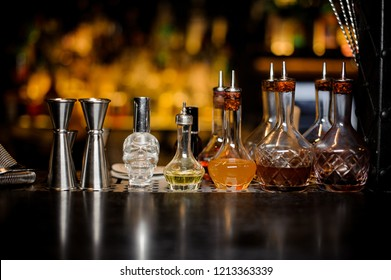 Set of elegant barman tools including jiggers and little bottles with liquor and bitters of different colors