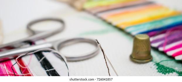 Set for embroidery: multi-colored thread, canvas, scissors.