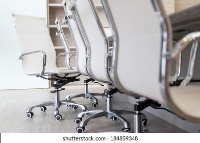 Set of empty office chairs next to long table in boardroom with low camera angle