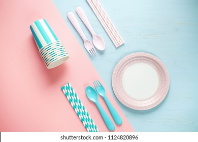 Set of empty, pastel paper tableware bowls, spoons and forks, straws  on color background. Untensils for a picnic. Flat lay. Top view